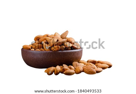 Peeled almonds in a clay plate isolated
