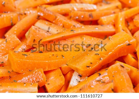 Peeled and sliced fresh organic carrots covered in olive oil and thyme prepared to be roasted in a ceramic tray