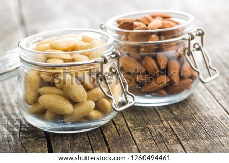 Peeled and unpeeled almonds in jar.