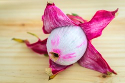 Peeled Dragon fruit on a wooden tabletop, edible nutritious white flesh part in the open close-up view.