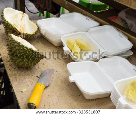 Peeled durian in pre-pack boxes, next to it is a knife, the tool to peel durian. Selective focus on the boxes, they are ready to sell as to-go, convenience fresh durian packs