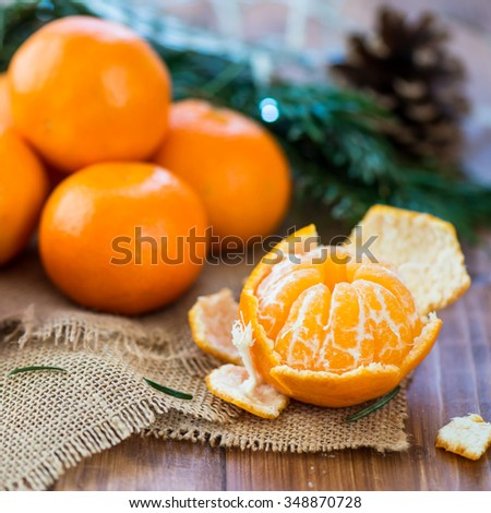 Peeled Fresh Clementine Tangerine on Brown Wooden Table with Xmas Lights and Tree Branches on the Background