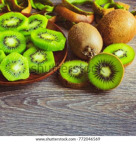 Peeled kiwi on a plate. Kiwi peeled and kiwi in the peel closeup. #772046569