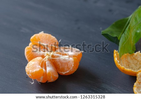 Peeled mandarin and peels are on wooden background #1263315328