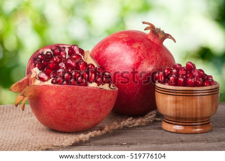 peeled pomegranate and whole with garnet grains in a bowl on wooden background #519776104