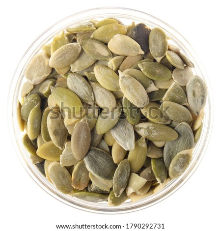 Peeled pumpkin seeds or pepitas in glass bowl isolated on white background flat lay closeup view Foto stock ©