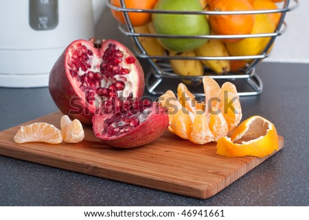 Peeled tangerine and cut pomegranate on the kitchen table