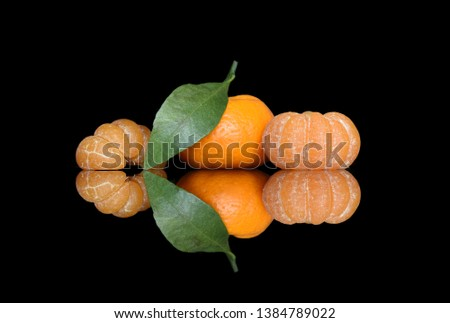 Peeled tangerines and tangerines in their skins with green leaves on black glass with bright and juicy reflection #1384789022