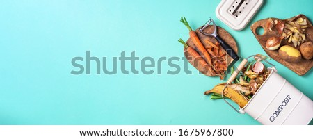 Peeled vegetables in white compost bin on blue background. Trash bin for composting with leftover from kitchen on blue background. Top view. Recycling scarps concept. Sustainable and zero waste Foto d'archivio ©