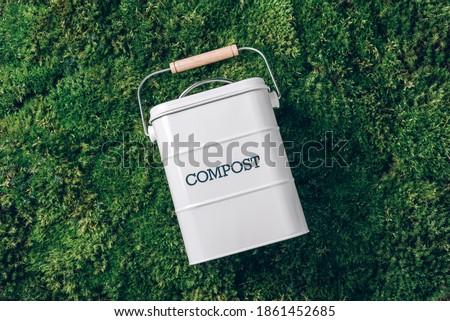 Peeled vegetables in white compost bin on green grass, moss background. Trash bin for composting with leftover from kitchen. Top view. Recycling scarps concept. Sustainable, zero waste lifestyle. Foto d'archivio ©