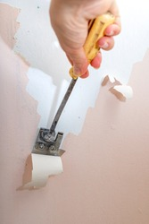 Peeling old latex paint off the wall. Using a scraper to renovate a bathroom. Place - renovation at home.