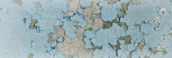 Peeling paint on the wall. Panorama of a concrete wall with old cracked flaking paint. Weathered rough painted surface with patterns of cracks and peeling. Grunge texture for wide panoramic background
