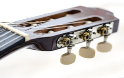 Pegs on the fingerboard of a guitar. Deteriorated and dusty acoustic guitar head and tuning keys. Macro, closeup, selective focus on the string