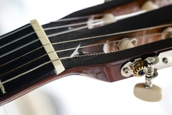 Pegs on the fingerboard of a guitar with a broken string. Deteriorated and dusty acoustic guitar head and tuning keys. Macro, closeup, selective focus on the string