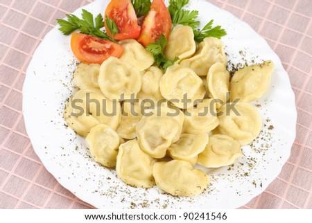 Pelmeni - traditional russian dish. Close up with tomato