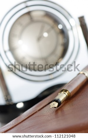 Pen, agenda and desk clock on office table against white background