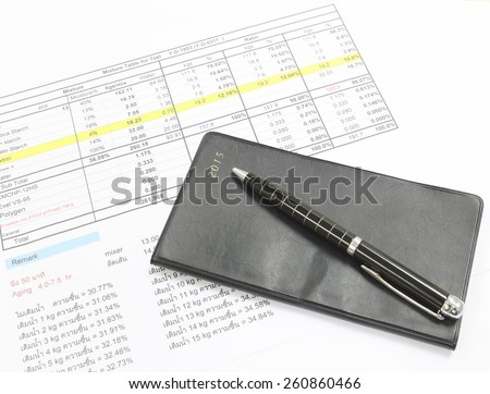 Pen and black notebook placed on the document.