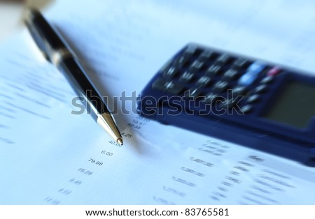 Pen and calculator on financial document - radial blur technique used