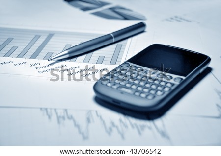 Pen and cell phone on a market report