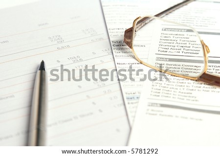 Pen and glasses on top of financial document. Shallow depth of field.
