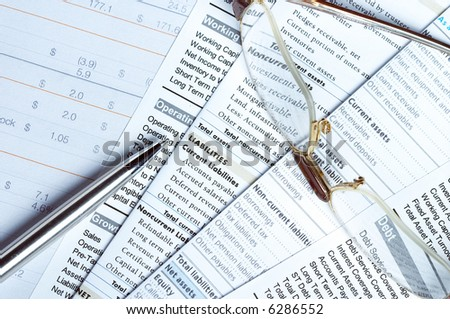 Pen and glasses on top of financial documents