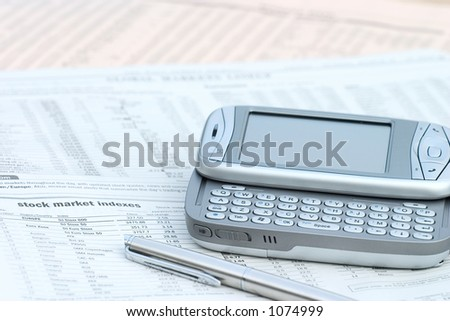 pen and mobile phone on top of a financial newspaper.