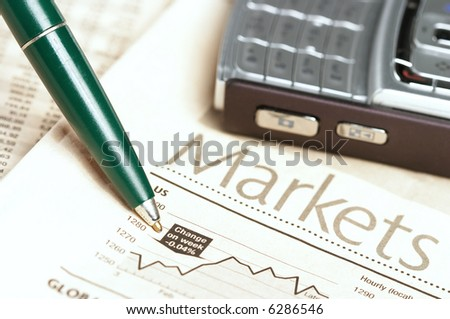 Pen and mobile phone on top of a financial newspaper