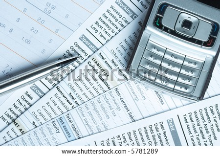 Pen and mobile phone on top of financial documents