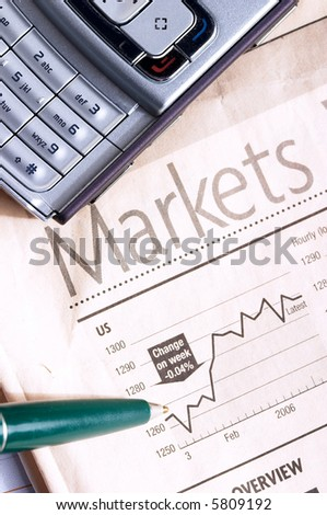 Pen and mobile phone over financial newspaper - stock photo