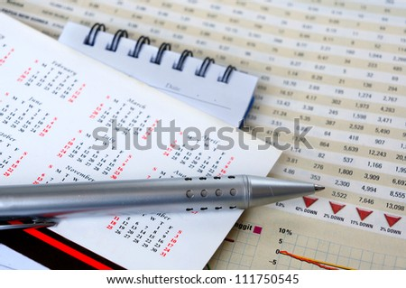 Pen and notepad on calendar for business concept