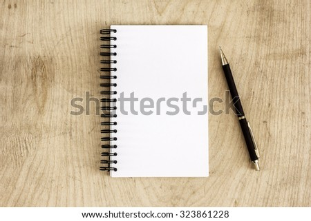 Pen and Notepad on the wooden desk./ Pen and Notepad on the wooden desk