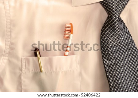 pen and tooth brush in businessman pocket
