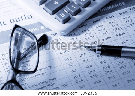 """pen, calculator and glasses on the newspaper with table """"Economic structure and performance"""" made with blue tones"""