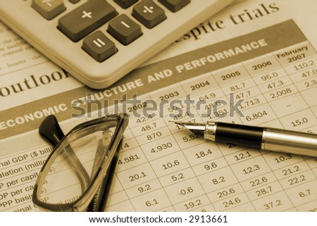 """pen, calculator and glasses on the table """"Economic structure and perfomance"""", made with sepia tones"""