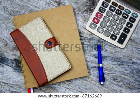 pen, calculator and notebook on wood texture