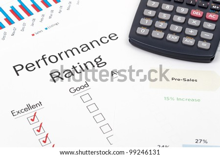 Pen, Calculator and Performance Rating Form on desktop in business office.