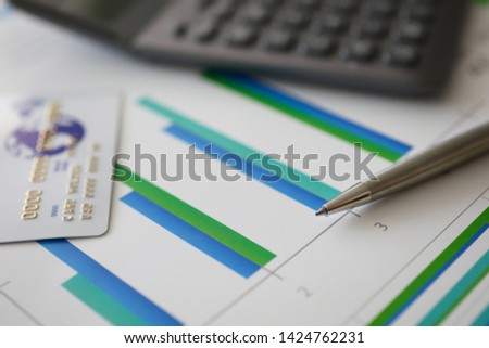 Pen calculator and plastic debit card are on table in office on background business graphs with color statistics statistics charts.