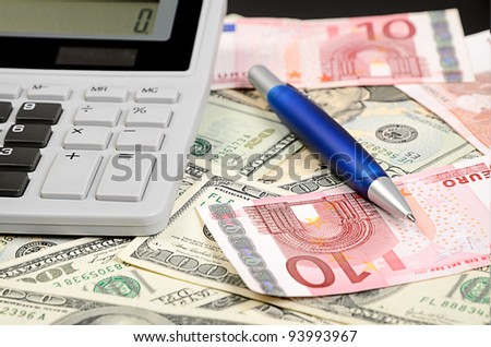 Pen, calculator on euro and dollar  banknotes