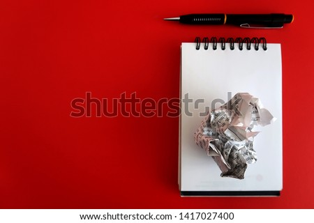 Pen ,crumpled paper and a blank notepad paper on red background with copy space. Concept of first time writing /writers block.