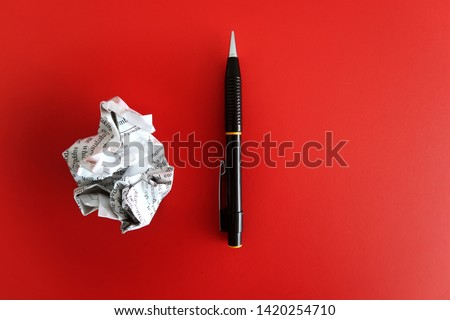 Pen ,crumpled paper on red background with copy space. Concept of first time writing /writers block.