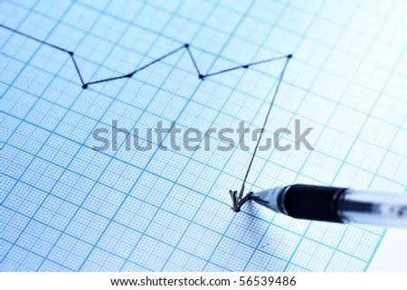 Pen drawing a profit graph. Shallow DOF!