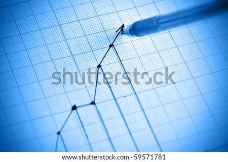 Pen drawing profit line graph. Shallow DOF!