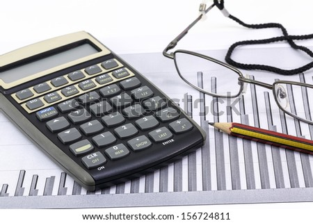Pen, glasses and calculator on paper table with finance diagram