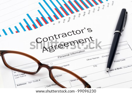Pen, Glasses and Contractor's Agreement Form on desktop in business office.