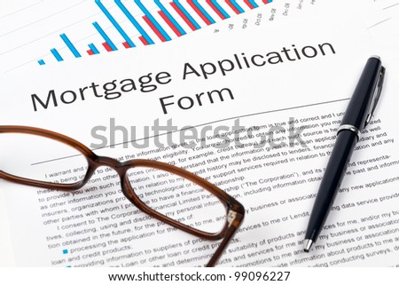 Pen, Glasses and Mortgage Application Form on desktop in business office. - stock photo