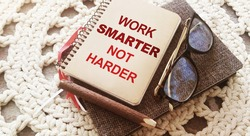 Pen,, glasses and spiral notebook with Work Smarter Not Harder words on crochet cloth background. Career and business concept