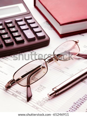 Pen,glasses,calculator and notebook close up