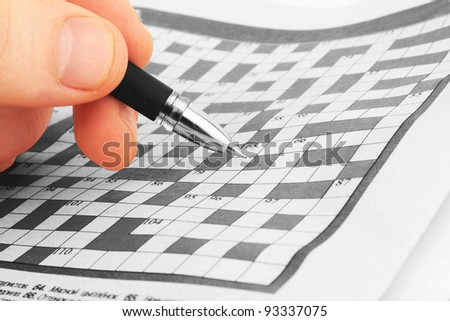 pen in a hand on a blank crossword to be filled