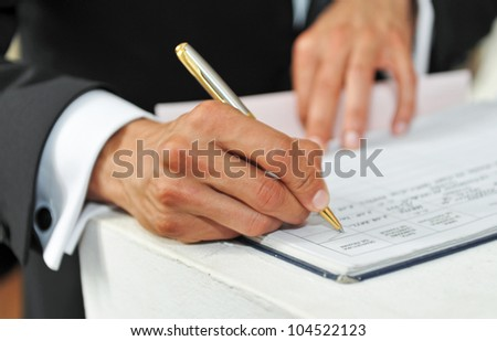 pen in hand of man writing on the notebook #104522123