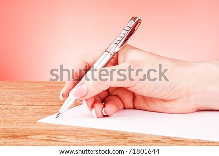 pen in hand writing on paper